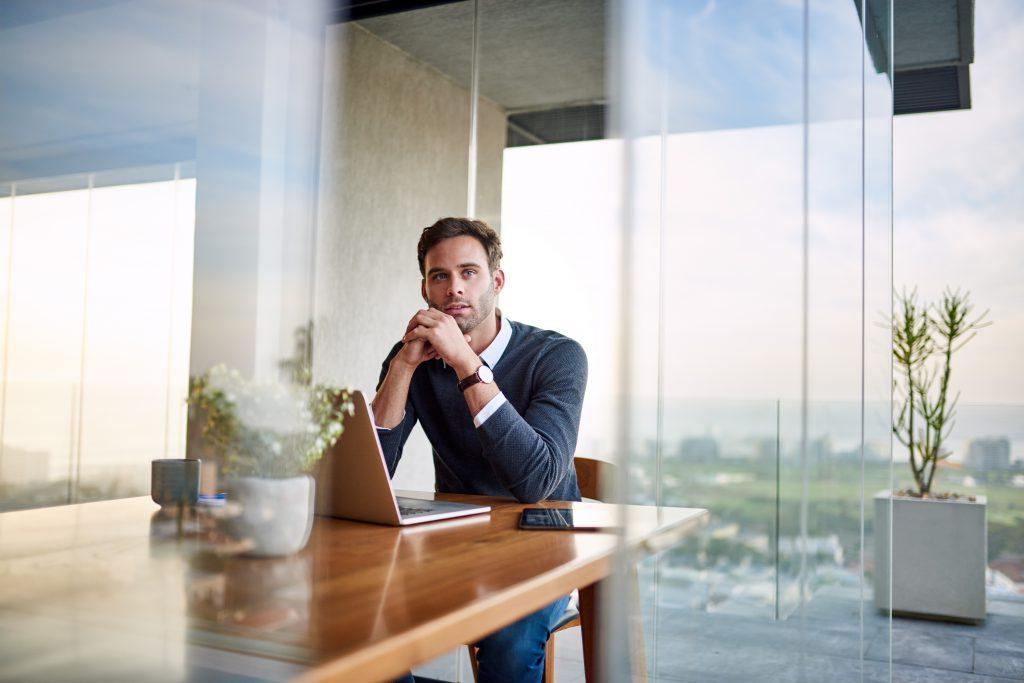 Mann im Büro am Laptop und Nachdenken